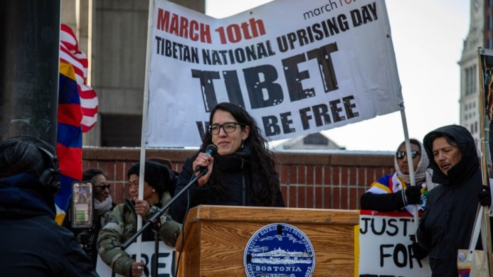 "A woman stands at a podium. Behind her is a sign that says ""Tibet will be free."""