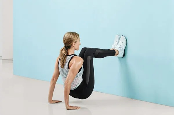 Works: arms, back, core Sit with heels on wall at knee level, palms on floor under shoulders, fingers facing wall. Press into floor to lift hips a few inches. Bend elbows, lowering body for 2 counts to hover 1 inch above floor (as shown); press back up for 2 counts. Continue for 1 minute. (Make it easier: Place one foot on floor.)