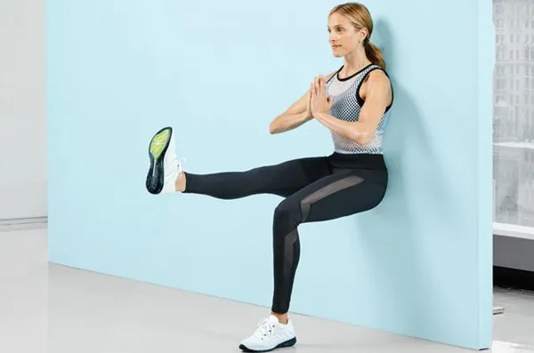 Works: core, butt, quads Sit with back against wall, knees bent 90 degrees. Lift and extend right leg at hip level (as shown). Hold for 30 seconds; then pulse left leg for 30 seconds. (Make it easier: Lower leg for pulses.)