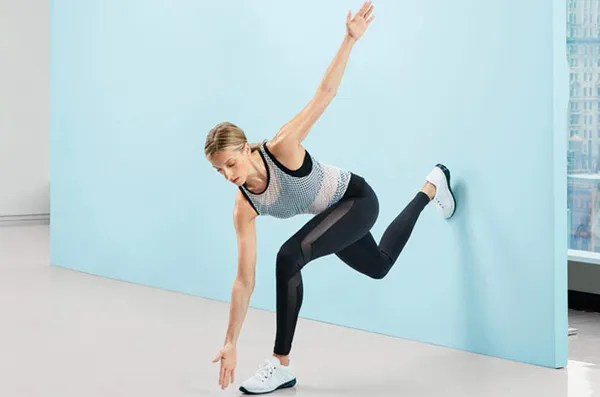 Works: core, butt, quads Stand with back about 3 feet from wall. Lift right leg and place toes on wall. Bend left knee deeply and extend arms. Twist torso left, bringing right hand to left foot (as shown). Turn back to center and straighten front leg over 4 counts. Continue for 2 minutes. (Make it easier: Don't twist.)