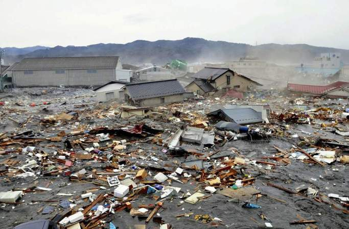 Houses, cars and other debris are washed away by tsunami tidal waves in Kesennuma in Miyagi Prefecture, northern Japan, after strong earthquakes hit the area Friday, March 11, 2011. (AP Photo/Keichi Nakane, The Yomiuri Shimbun)