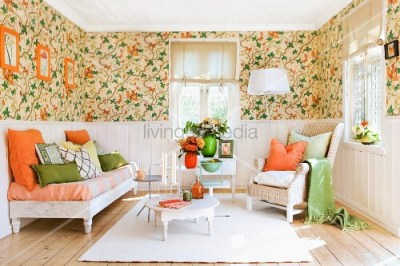 Lounge area with floral wallpaper above dado rail, white wall panelling below and orange and ...