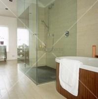 Begehbare Dusche mit Glaswand neben einer frei stehenden ...