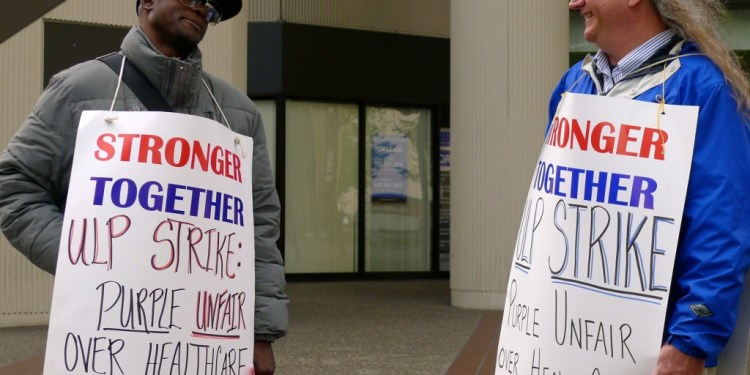 ASLIU supporters Anthony and Earl picket outside of Purple Communications in Oakland as part of a one-day Unfair Labor Practice strike. Purple has been charged with violating workers' rights in its video relay services.