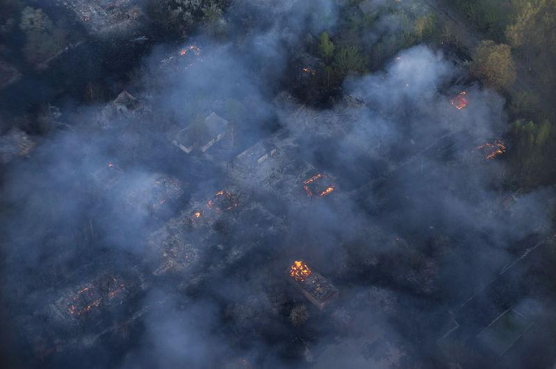 An aerial view from a helicopter shows fire and smoke in northern Ukraine