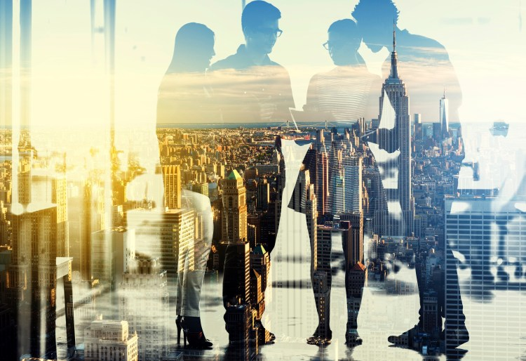 Multiple exposure shot of a group of businesspeople superimposed over a city background