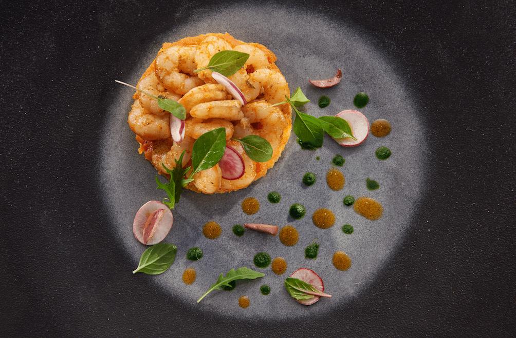 Crevettes à la chermoula et zaalouk de tomates aux aromates sur une harcha, éclat végétal.