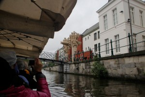 Tourists enjoy taking pictures of the medieval art and architecture along the banks of the Leie River.