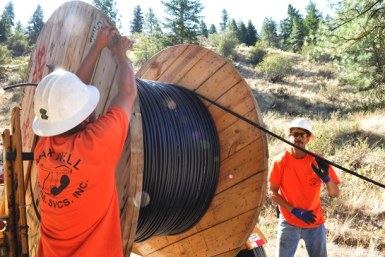 Kyle Thomas, left, and Rico Carralho roll out the big spool. Photo by Sue Misao