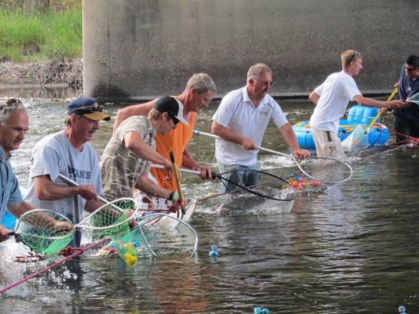 Volunteers gather at the finish line to make sure no duck escapes further down the river. Photo by Don Nelson