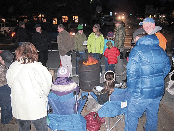 Visitors taking advantage of the day's activities gathered around several burn barrels along Riverside Avenue to stay warm while waiting for the fireworks to begin. Photo by Don Nelson