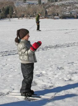 Delia Welcker, 4, of Spokane, takes a break from skiing with her family on Patterson Lake to watch a nearby ice fisherman.Photo by Darla Hussey