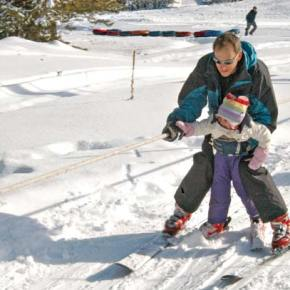 Mark Roman, Winthrop, gives 3-year-old daughter, Camille, a little assistance with the rope tow during the first full weekend of skiing at the Loup Loup Ski Bowl. It was Camille's first day on skis. Photo by Mike Maltais