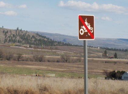 Some county roads, like Old Highway 97 outside of Okanogan, have been marked with signs banning ATVs. Photo by Marcy Stamper