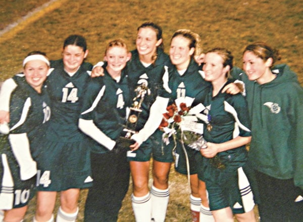 Seniors Addie Estes, left, Kelsey Bourn, Katie McCurry, Regan Walsh, Kate Honsinger, Madison Bradshaw and Lindsay Welfelt celebrate the fourth-place state trophy the Lady Lions' soccer team won in 2003. Photo courtesy of LBHS yearbook