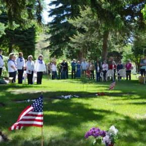 Dozens of valley families and American Legion Auxiliary members stand at attention during the Memorial Day ceremony at Sullivan Cemetery. Photo by Laurelle Walsh