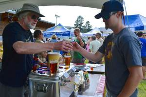 Curtis Koger, left, father of OSB's brewmaster, serves up Ruud Awakening IPA. Photos by Laurelle Walsh