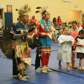 Dancers Ron Friedlander, left, and his grandson (and former Paschal Sherman student) Josiah Moses, were part of the powwow in the gym as students and festival-goers joined in. Paschal Sherman first grader Daeshia Marchand danced in her bare feet, along with two girls who came to the festival from another school. Photo by Marcy Stamper