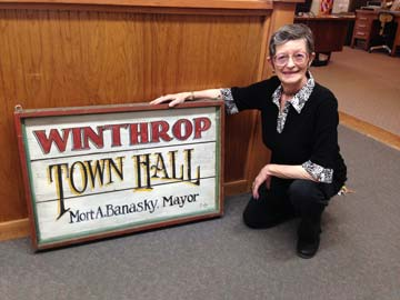 Mort Banasky recently posed at Town Hall with a sign from her days as mayor of Winthrop. Photo courtesy of Kristen Smith