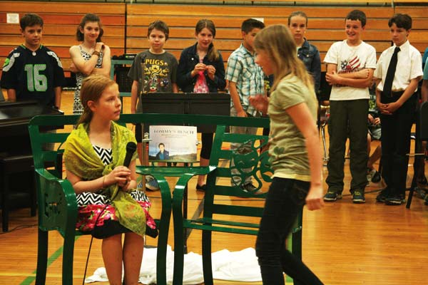Photo by Marcy Stamper In a skit showing how the bench might be used, fifth-grader Lucinda Tobiska, feeling excluded from a ball game, sits on the bench as classmate Rhain Hagan comes by to chat.