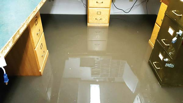 Photo courtesy of Michelle Gaines At least 3 inches of dirty water gushed into the Winthrop Marshal's basement offices during an unusually heavy rainstorm last week. Staff scrambled to unplug computers and empty file drawers.