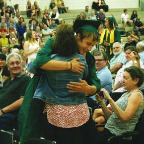Photo by Darla Hussey On their way to the stage, graduates pause to hug loved ones.