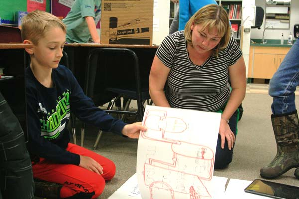 """Photo by Marcy Stamper Fourth-grade teacher Tiffany Surface helped Vance Nielsen with his project about nuclear energy, part of an IB unit on """"How the World Works."""""""