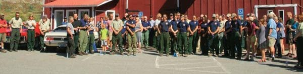 Photo by Marcy Stamper Forest Service employees, firefighters and community members observed a moment of silence on the one-year anniversary of the entrapment that took the lives of three firefighters and seriously injured a fourth in the early hours of the Twisp River Fire. Lights flashed on two Forest Service engines as the tribute was announced over the dispatch system.
