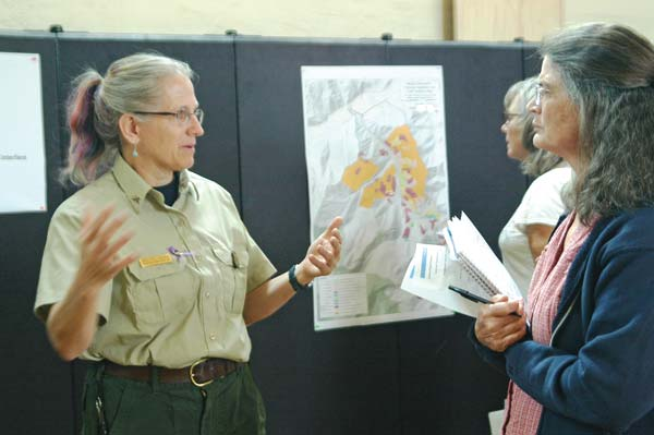 Photo by Ann McCreary Meg Trebon, leader of the Mission Project interdisciplinary team, discusses proposals for tree thinning and prescribed burning with Libby Creek resident Pema Bresnahan at an open house hosted by the Methow Ranger District.