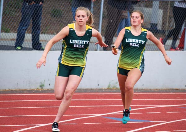Photo by Erik Brooks Lauren Fitzmaurice, left, takes the baton from Haley Post in the 4x200-meter relay at the district meet last weekend.