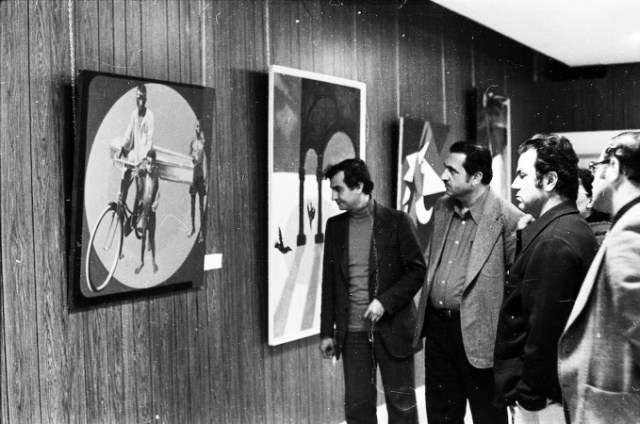 Ezzedine Kalak guides a tour for PLO officials at the exhibition opening, Visible artwork (L-R): Gontran Guanaes Netto (Brazil), and Naim Ismail (Syria)