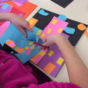 Child cutting out shapes with scissors for a paper collage