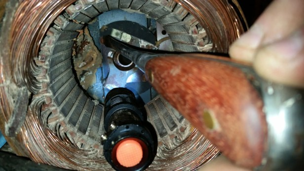 View through stator of left end frame with centrifugal switch in center. Dirt dauber nest to left.