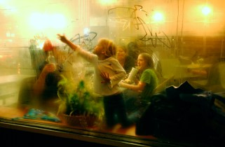 Katelyn Pagdin, 5, draws in the condensation on the window at the Subway on Watertown's Public Square as sister Rachel, 9, watches on Wednesday night, 2003. The Pagdin family, including father Grant, mother Valerie and sister Emma, 7, were eating dinner together. - The Watertown Daily Times