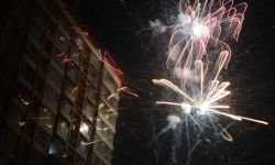 Fireworks explode in dark sky next to illuminated building