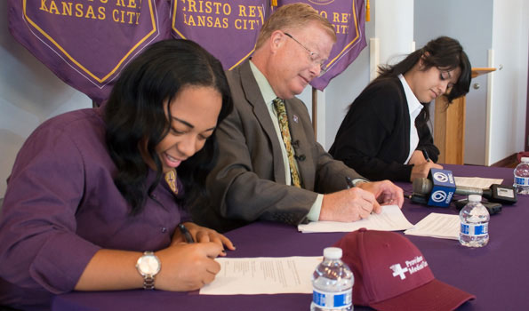 Cristo Rey students Alexus Williams, Samantha Ballesteros and Providence Medical Center CEO Randall Nyp signed an agreement that began the students' work program at the hospital this year.