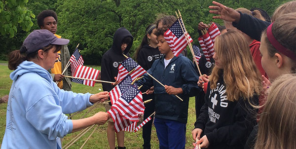 Students from Academie Lafayette have clean up and placed flags at neglected African American Highland Cemetery.