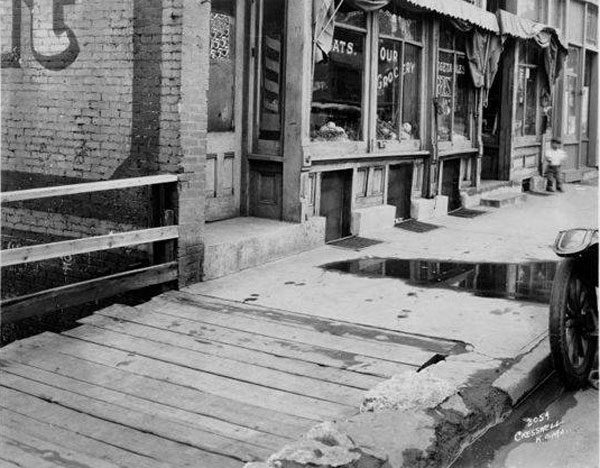 In 1929, this section of 12th Street between Euclid and Garfield, showed one of the problems the city struggled with in trying to keep its sidewalks in good order: one property owner chose a wooden sidewalk, while the owner next door choose cement. Water standing on the street and decayed curbs also show that poorly maintained sidewalks are not a new problem. Courtesy Kansas City Public Library/ Missouri Valley Special Collections.