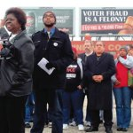Anita-Johnson-points-toward-Voter-ID-Suppression-billboards-at-press-conference-cropped
