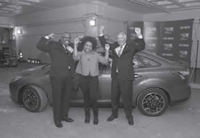 Pictured in Car Winner Photo are (L to R) - Chuck Harvey of Johnson Controls, Linda Stewart of Milwaukee winner of theGive and Win Sweepstakes prize: A NEW 2013 Ford Focus 4-Door Sedan SEL donated by Johnson Controls and Bruce McDonald of Johnson Controls.