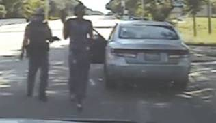 Texas trooper Brian Encinia holds up a Taser as Sandra Bland steps out of her car in a video that some have questioned as having been edited