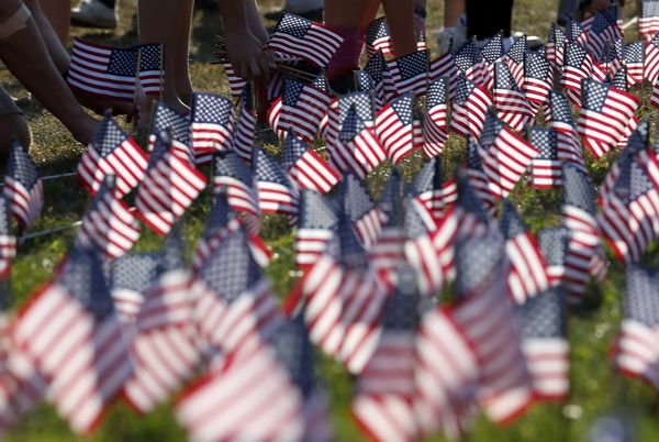 People plant some of the 3000 U.S. flags placed in memory of the lives lost in the September 11, 2001 attacks, at a park in Winnetka, Illinois, September 10, 2013.   REUTERS/Jim Young   (UNITED STATES - Tags: DISASTER ANNIVERSARY SOCIETY)