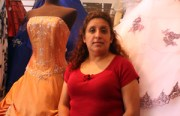 Gloria Martinez poses in front of dresses (photo by Rigoberto Hernandez)