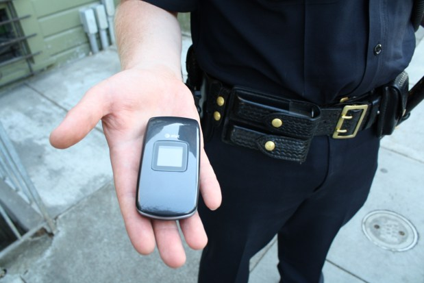 Officer Nathan Bernard displays his cell phone in Bernal Heights.
