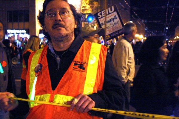 A union member holds caution tape, blocking traffic.