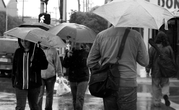 Young people walk together under umbrellas down Mission Street