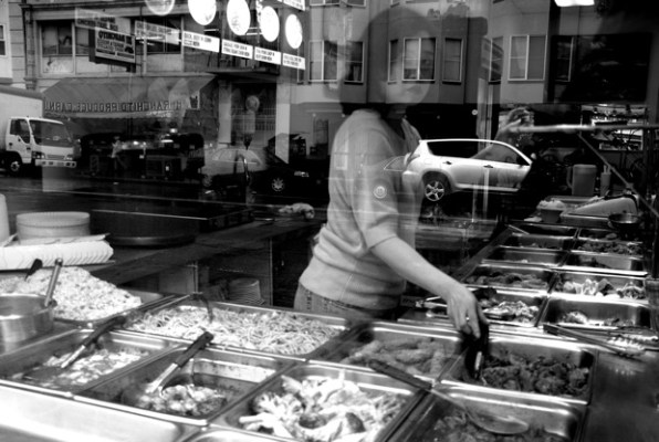 A woman looks out of the window from Wan Kee Restaurant on Mission Street