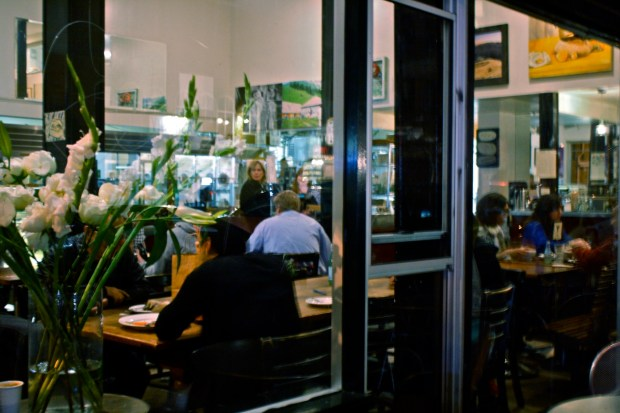 Looking through the picture windows of Tartine, a place where food is shared.