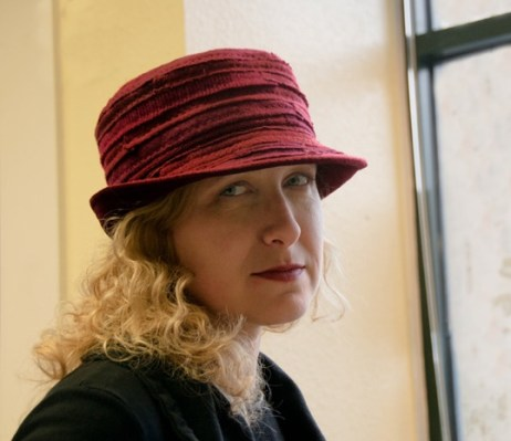 Elina Techkova of ADS Hats in one of her Alterknitive® recycled cashmere brim hats in shades of red.