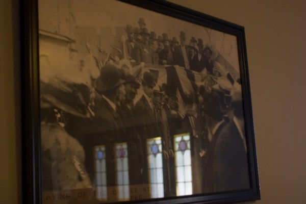 Original stained glass doors in the 1908 building can be seen reflected in a photo of the laying of the cornerstone.